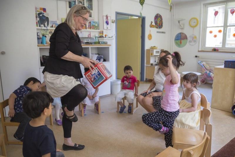 Einstieg in die Schullaufbahn: In einer Spielgruppe zeigt eine Gruppenleiterin eine Purzelbaum-Figur vor