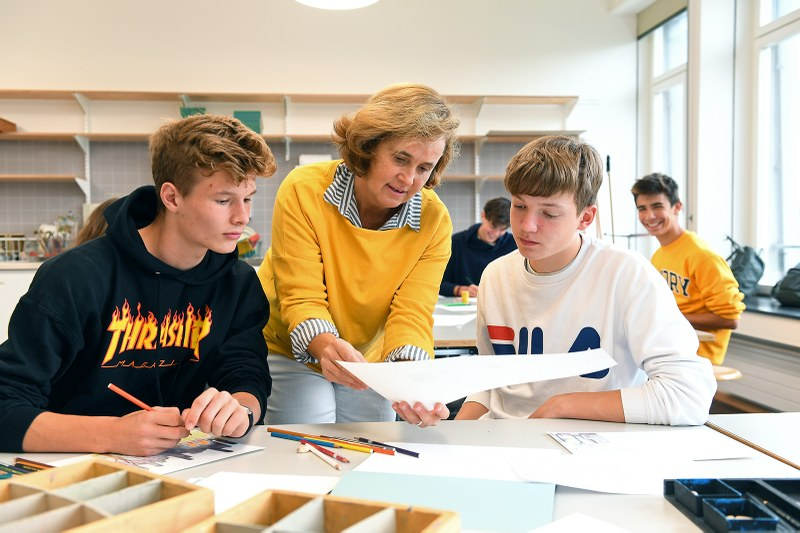 Bildnerisches Gestalten am Gymnasium: Eine Lehrperson unterstützt zwei Schüler.